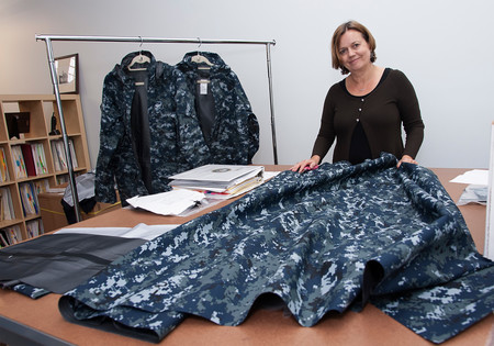 Clare King, president of Propel LLC, handling the material used to make one of the coats they are producing for the US Navy. The coats are produced with limited thread & needle, instead they are made using bonding and welding of the material. PBN PHOTO/ MICHAEL SALERNO